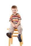 Petit garçon s'asseyant sur des selles Images stock