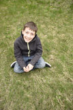 Petit garçon s'asseyant sur l'herbe Image stock
