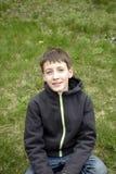 Petit garçon s'asseyant sur l'herbe Photographie stock libre de droits