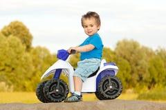 Petit garçon s'asseyant sur la quarte de jouet Image libre de droits