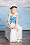 Petit garçon s'asseyant sur la valise image libre de droits