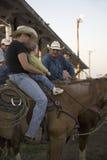Petit garçon s'asseyant sur le cheval avec le cowboy au rodéo de PRCA Photo libre de droits