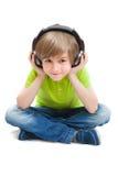 Petit garçon s'asseyant sur le plancher blanc écoutant la musique Photos stock