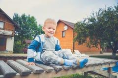 Petit garçon s'asseyant sur un banc photos libres de droits