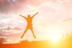 petit garçon sautant et ayant le temps heureux, concept de Sillhouette Photo stock