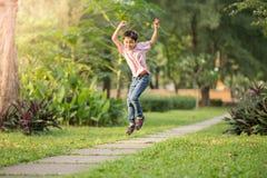Petit garçon sautant et courant en parc extérieur Photographie stock