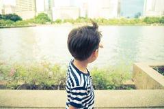 Petit garçon se réveillant près du lac en parc Photos libres de droits
