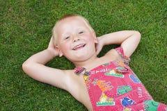 Petit garçon se situant dans l'herbe Photo stock