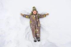 Petit garçon se situant dans la neige et rire Image libre de droits