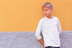 Petit garçon se tenant près du mur jaune et regardant loin image libre de droits