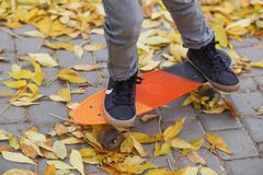 Petit garçon se tenant sur une planche à roulettes orange dehors Ima de plan rapproché Photos libres de droits