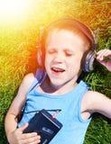 Petit garçon se trouvant sur l'herbe avec le vieux joueur de cassette sonore photo libre de droits
