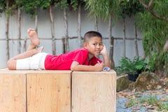 Petit garçon se trouvant sur le stylo de participation de main de boîte en bois regardant c photos stock