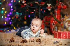 Petit garçon se trouvant sur son estomac dans la chambre avec le décor de Noël images stock
