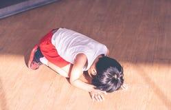 Petit garçon se trouvant vers le bas pleurant avec l'effort et tristesse image stock