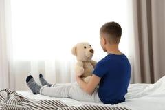 Petit garçon seul s'asseyant sur le lit dans la chambre Image stock