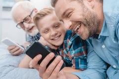 Petit garçon, son père et grand-père se trouvant sur le lit photos libres de droits