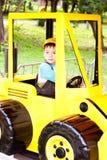 Petit garçon souriant et jouant dans le véhicule de jouet Image libre de droits