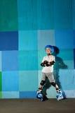 Petit garçon sportif mignon sur le rouleau se tenant contre le mur bleu de graffiti Images libres de droits