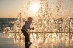 Petit garçon stupéfait essayant de courir à partir des vagues énormes au coucher du soleil de mer photo libre de droits