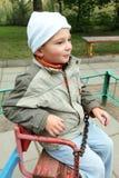 Petit garçon sur l'oscillation de roulement regardant de côté photo libre de droits