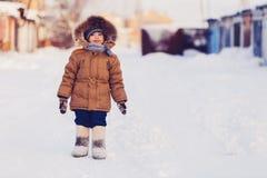Petit garçon sur la route neigeuse d'hiver Image stock