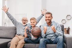 Petit garçon sur le divan avec le grand-père et le père, encourageant pour un match de basket et tenant a image stock