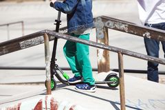 Petit garçon sur le panneau de scooter dans la rampe du parc de patin Photo libre de droits