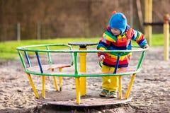 Petit garçon sur le terrain de jeu en automne Images stock