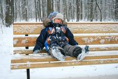 Petit garçon sur un banc pendant l'hiver Photo libre de droits