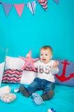 Petit garçon sur un fond de décor de mer avec un jouet Photo libre de droits