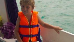 Petit garçon sur une sensation de bateau de plongée nerveuse avant son premier naviguer au schnorchel en mer ouverte banque de vidéos
