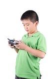 Petit garçon tenant un à télécommande par radio (combiné de contrôle) pour l'hélicoptère, le bourdon ou l'avion d'isolement Photographie stock libre de droits