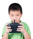 Petit garçon tenant un à télécommande par radio (combiné de contrôle) pour l'hélicoptère, le bourdon ou l'avion d'isolement sur l Photographie stock