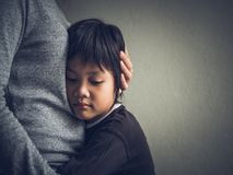 Petit garçon triste étreint par sa mère à la maison Photos stock
