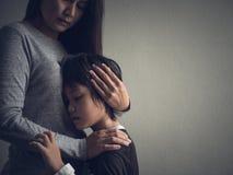 Petit garçon triste étreint par sa mère à la maison Photo stock