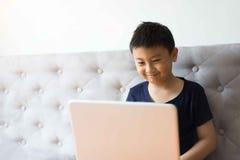Petit garçon utilisant le jeu de jeu d'ordinateur portable à la maison pour détendre image stock