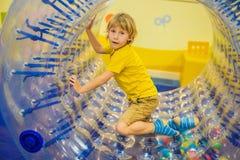 Petit gar?on mignon, jouant dans Zorb un anneau en plastique de cylindre de roulement avec un trou au milieu, intdoor photo libre de droits
