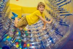 Petit gar?on mignon, jouant dans Zorb un anneau en plastique de cylindre de roulement avec un trou au milieu, intdoor image libre de droits