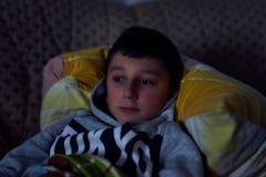 Petit gar?on sur le divan regardant la TV photos stock