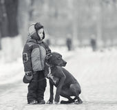 Petit garçon avec le grand chien noir Image libre de droits