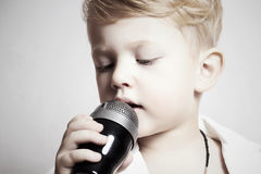 Petit garçon chantant dans microphone.child dans karaoke.music Image stock