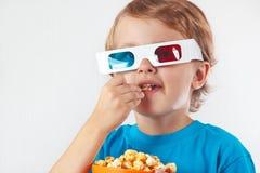 Petit garçon en verres stéréo mangeant du maïs éclaté Image stock