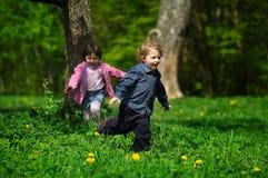Petit garçon et fille exécutant loin Image libre de droits