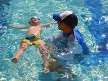 Petit garçon flottant avec l'instructeur de bain Photographie stock libre de droits