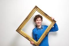 Petit garçon heureux tenant le cadre de tableau Photos libres de droits