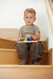 Petit garçon jouant sur des escaliers Images stock
