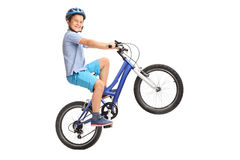 Petit garçon joyeux exécutant un wheelie avec son vélo Photographie stock libre de droits