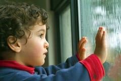 Petit garçon observant la pluie Photographie stock
