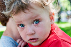 Petit garçon pleurant à sa mère dans des ses bras Photographie stock libre de droits